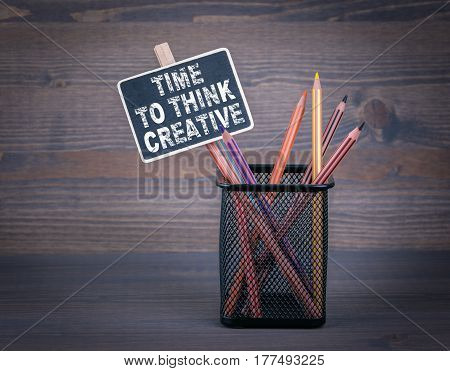 Time to think creative. A small blackboard chalk and colored pencil on wood background.