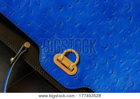 Texture of genuine leather close-up with embossed under the skin of Ostrich, gold lock, fashion blue color. For background, backdrop, substrate, composition use. With place for your text