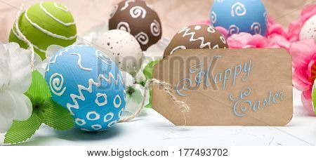 Painted easter eggs and branches of spring sakura closeup on a light blue background with space for congratulation, border design panoramic banner