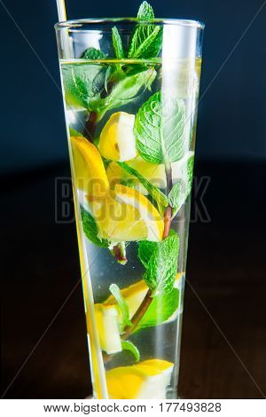 Close Up Glass Of Lemonade With Mint And Lemon Wedges On The Dark Background. Selective Focus