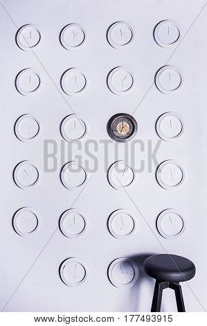 Black leather bar stool near white wall with identical round white not numeral clocks and one unique dark clock. Design concept