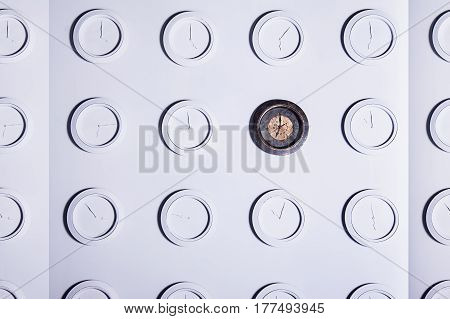 White Wall With Identical Round White Not Numeral Clocks And One Unique Dark Clock. Time Concept Bac
