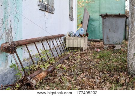 A rusty climbing ladder lies on the ground along an old building in the background of a garbage can