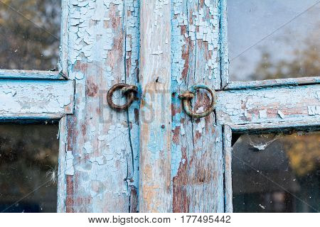 Eyelets castle on the old wooden door is blue the paint is crumbling