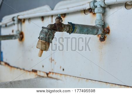 Rusty washbasin faucet on white background with rust elements