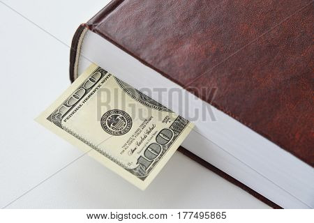 Dollar bill used as a bookmark in a book.