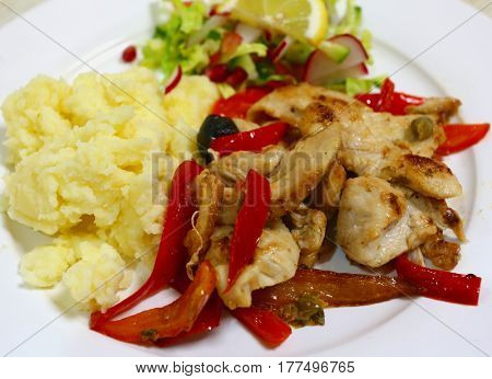 Stir fried chicken tenders and red capsicum slices cooked with olives and capers and served with mashed potato and a chopped salad