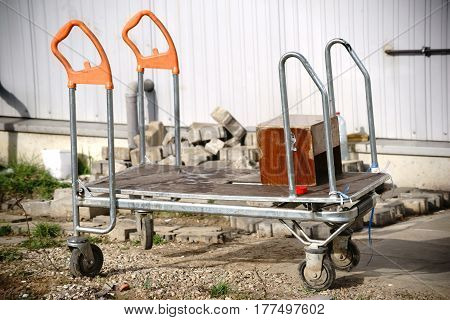 A worn luggage carrier is used for tool transport and material transport.
