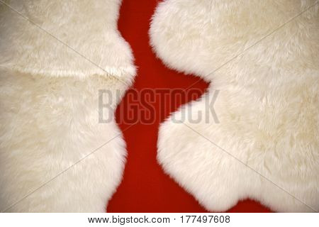 The close-up of the white fabric fluffies of a bedside carpet made of animal fur.
