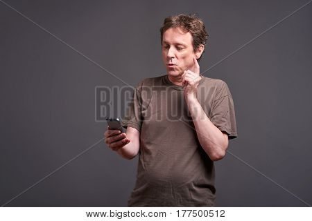 A middle age man standing and using a smartphone