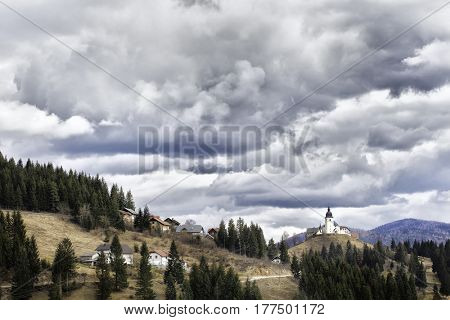 Small church on a hilltop in Slovenia. A rural landscape with thick clouds and dense forests surrounding the village.