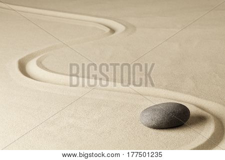 Japanese zen garden stone with line in sand. Balance and harmony for relaxation and meditation. Spa wellness background.