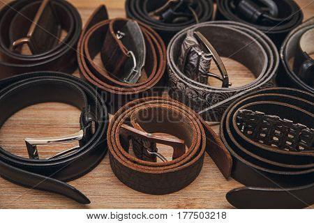 Background from many leather belts.Different colors.Wooden background.