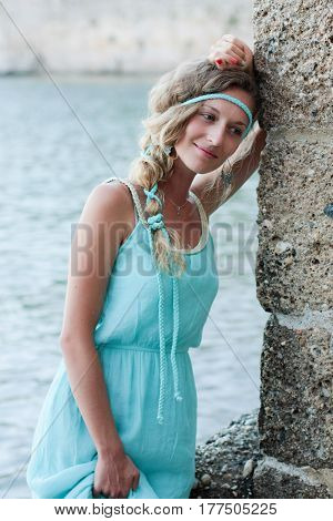 Young Woman Thinking And Standing With Blurred Sea And Medieval