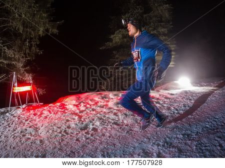 ALMATY, KAZAKHSTAN - 18 FEBRUARY 2017: Night competitions in the foothills of the city of Almaty, in the Trailrunning and Skyship discipline, which is called TunRun winter edition. Man running in the mountains at night.