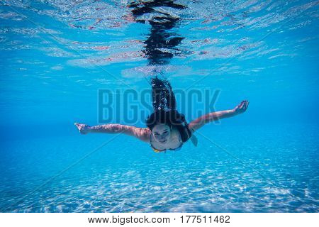 young girl dive with open eyes in the swimming pool, underwater shoot