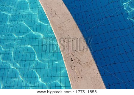 Natural background - blue and dark blue water in the empty pool with separation barrier