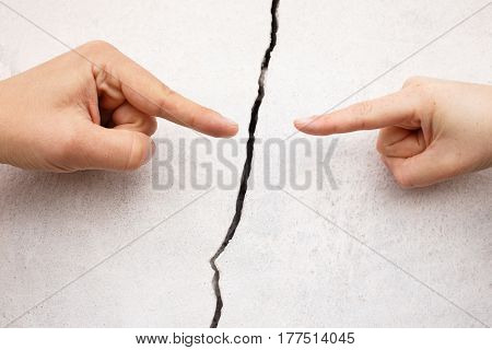 fingers pointing each other on the background of crack in the concrete wall