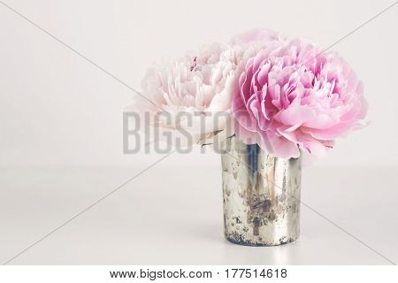 romantic still with a small bunch of pink and white peonies in a vintage silver vase on a white table - pastel colored retro overlay, copyspace