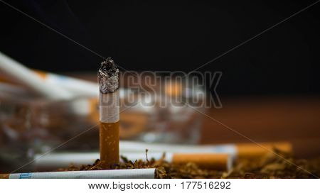 Closeup cigarettes and tobacco lying inside and around glass ash tray on wooden surface, anti smoking concept.