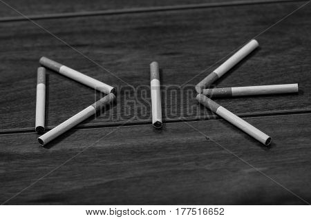 Cigarettes lying on wooden surface shaped into the word die, artistic anti smoking concept, black and white edition.