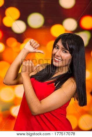 Brunette model posing happily in front of blurry lights background, interacting using hands.