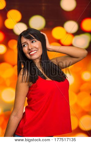 Brunette model posing happily in front of blurry lights background, touching hair using hands.