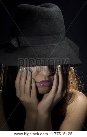 Young girl hiding her face under hat