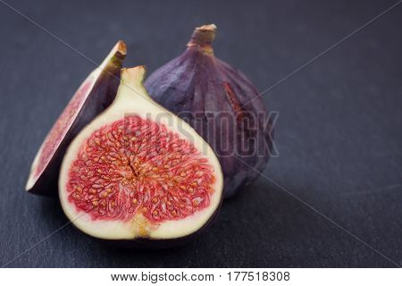 Fresh figs on a black table .