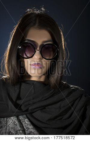Young girl with shawl and glasses on black background