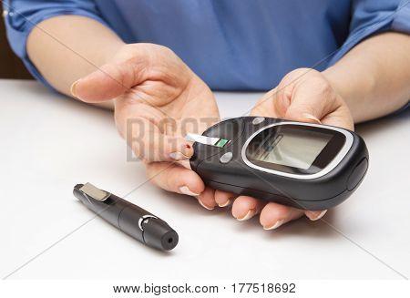 Closeup female hands using glucometer scanner on finger with blood sample