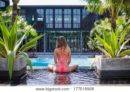 Serene meditating woman relaxing at luxury travel holiday vacation resort. Happy blissful young woman in bikini in meditation enjoying summer sun and tanning at Spa resort