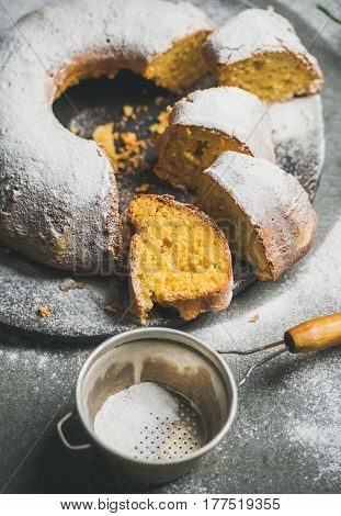 Homemade gluten-free lemon bundt cake with sugar powder over grey concrete background, selective focus, vertical composition