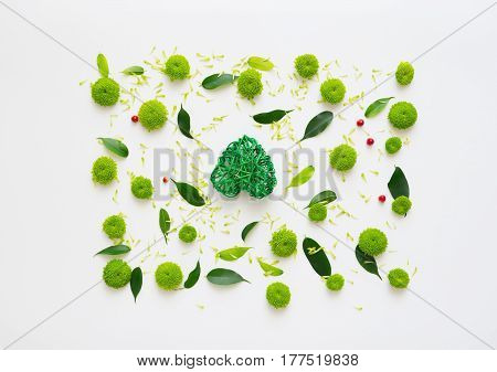 Heart with pattern from petals of chrysanthemum flowers, ficus leaves and ripe rowan on white background. Overhead view. Flat lay.