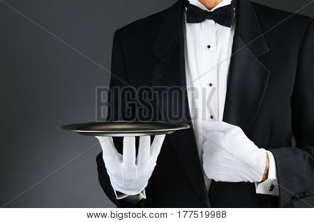 Closeup of a tuxedo wearing waiter holding a silver tray in front of his body. Horizontal format on a light to dark gray background.