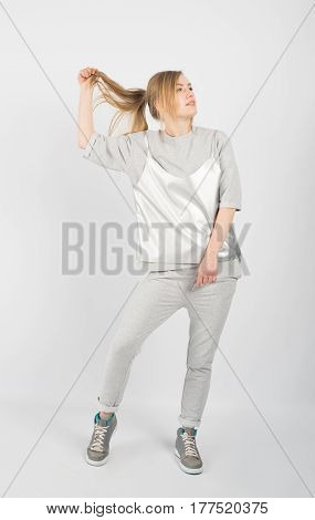Young hipster girl wearing grey clothes and sneakers posing isolated on white background. She is holding hair up