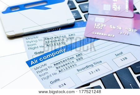 Buying airline tickets online for travel with credit cards and laptop on keyboard background