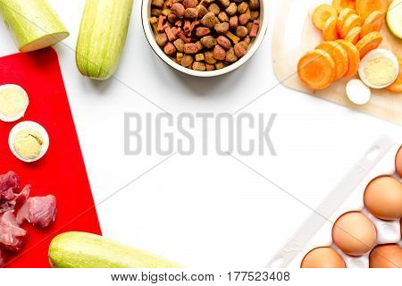 Fresh sliced vegetables and dry petfood on white kitchen table background top view mockup