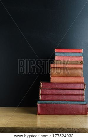 A pile of old used text books stacked in a pile on a wooden desk in front of a black chalkboard. Copy space to left and above.
