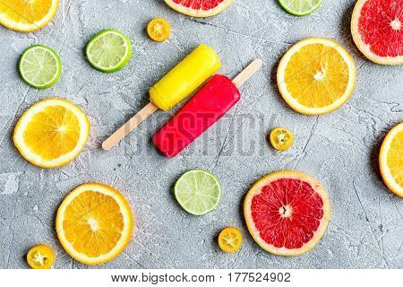 fresh citrus slices with fruit popsicles on stone table background top view pattern
