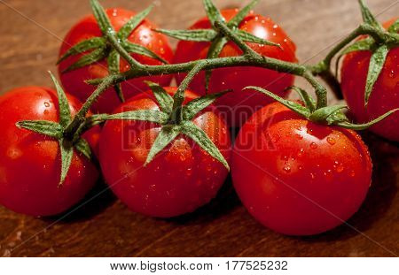 fresh ripe wet cherry tomatoes on wooden background