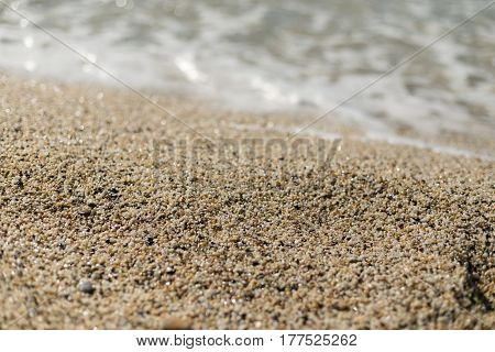 Beautiful sand at Cleopatra beach in Alanya turkey with sand in center of image in sharp focus and blurred wave and sand on foreground and background.