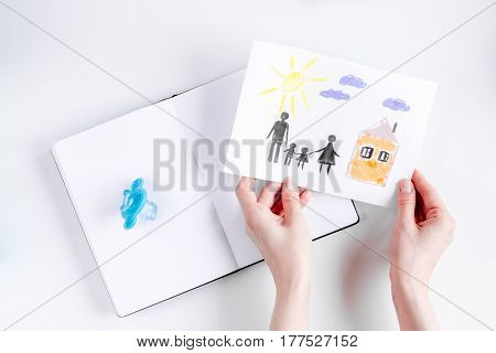 happy family concept with children drawing and notebook on white desk background top view