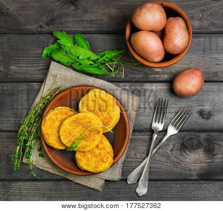 Roasted vegetable potatoes Healthy cutlets on plate. Vegetarian lunch or dinner recipe. Spices for potato patties (fritters) Thyme arugula raw potatoes. Gray wooden background. Top view