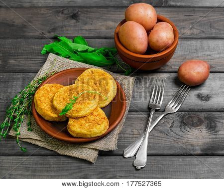 Roasted vegetable potatoes Healthy cutlets on plate. Vegetarian lunch or dinner recipe. Spices for potato patties (fritters) Thyme arugula raw potatoes. Gray wooden background.