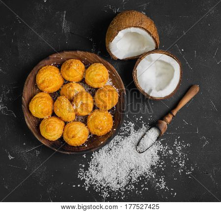 Coconut dessert biscuits (cookies) on a wooden plate. Ingredients for cookies (biscuits) fresh chopped coconut and coconut chips. Dark black concrete table background. Top view from above and copy space.