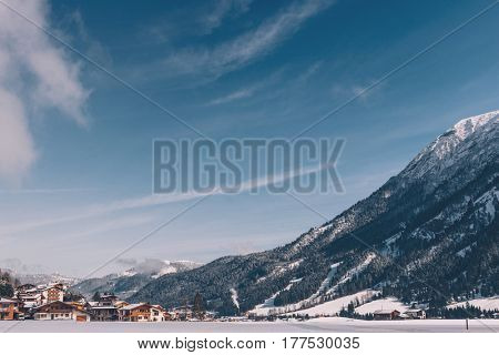 Alpine ski resort with wooden chalets in a snowy valley with frozen lake below high mountain peaks in picturesque scenery