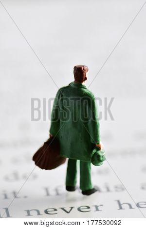 miniature traveler man seen from behind carrying a suitcase and a hat placed on an e-book reader
