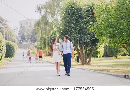 mom dad and little daughter walking in a sunny park