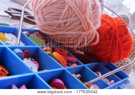 Box with accessories for knitting. Box with cells of blue color. On a box two balls of wool. Indoors. Horizontal format. Color. Photo.